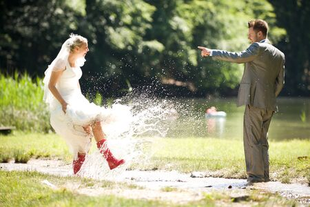 bride and groom splashing water in the nature trash the dress