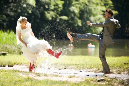 bride and groom splashing water in the nature trash the dress photo