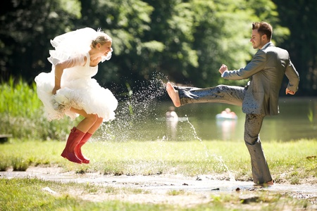 ring wedding: bride and groom splashing water in the nature trash the dress