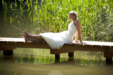 bride in the nature sitting on a bridge on a lake Stock Photo