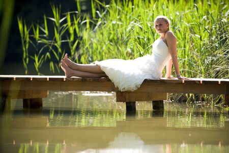 weddingrings: bride in the nature sitting on a bridge on a lake Stock Photo