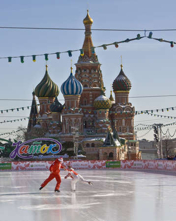 Moscow, skating-rink on Red square, St. Basil's (Pokrovskiy) cathedral and Spasskaya Kremlin tower.  Moscow, Red square with St. Basil's (Pokrovskiy) cathedral and Spasskaya Kremlin tower. In winter Red square changes in a big skating-rink, remaining from