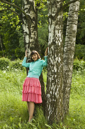Young woman (brunette, caucasian) standing near birch trees in park, summer. Stock Photo - 12019152