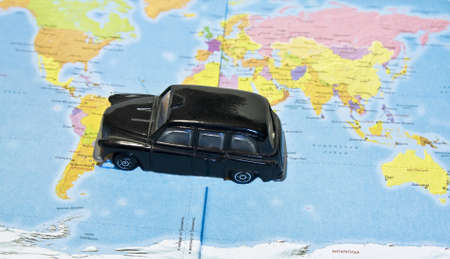 Little toy black car standing on map of the world. photo