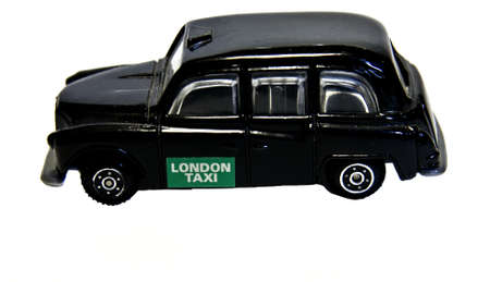 Souvenir little toy black London taxi isolated on white background.
