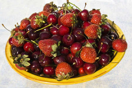 coi: Plate with many red cherries and strawberry.