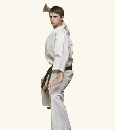 Young karateka, European boy, in white kimono isolated. photo
