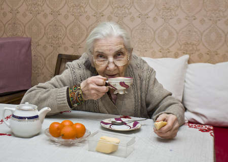 woman eat: Old lady (European) drinking tea at home. Stock Photo