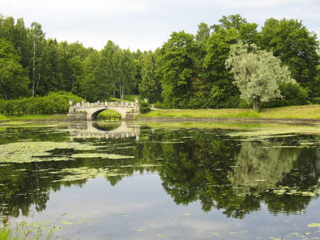 Summer landscape with little bridge on river, recorded in park in Pavlovsk, surroundings of St. Petersburg, Russia. photo
