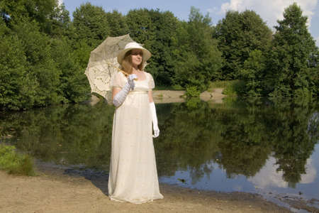 Young woman in white historical dress of XIX century with white umbrella in white hat near lake. photo