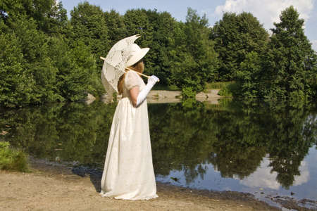 Lady in white historical dress with white umbrella standing near lake in park.