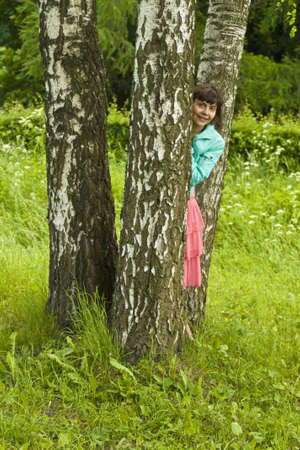 Young woman (Caucasian, brunette) standing in park near birch trees. Stock Photo - 13329342