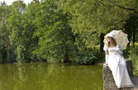 Young lady in white historical dress with white umbrella near lake in park. photo