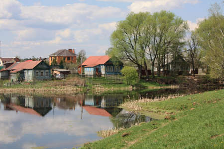 Landscape with wooden village houses near lake, trees, reflection in water. Recorded in Russia, villiage in Moscow region. Typical houses and nature of the country. Stock Photo - 14126504