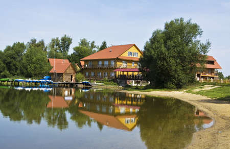 Wooden country houses near lake with reflection. Recorded in Moscow region.