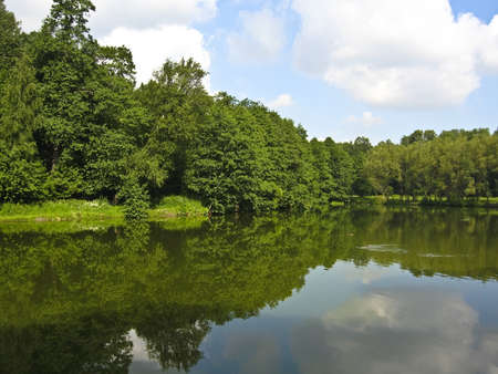 Summer water landscape - lake, forest on banks, reflection of trees and sky with clouds in water Stock Photo - 14248143