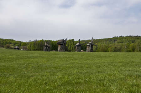 Wooden windmills on green meadow, recorded in outdoors museum of national architecture in Pirogovo, near Kiev, capital of Ukraine Stock Photo - 14248225