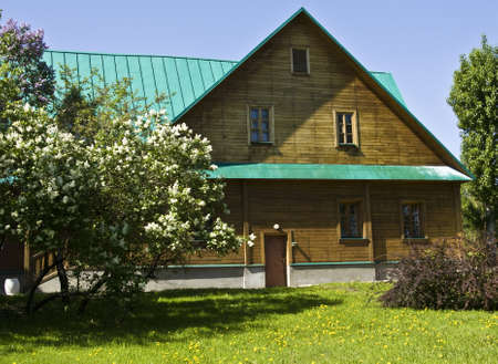 Moscow, Russia - May 22, 2011: Wooden village house with white lilas, Russia.