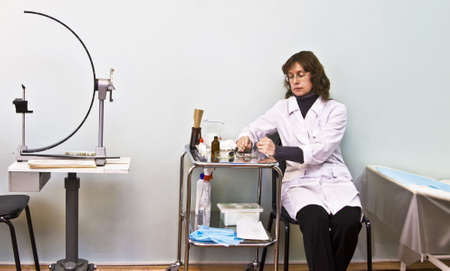 perimeter: Doctor-ophthalmologist at work in cabinet and medical apparatus