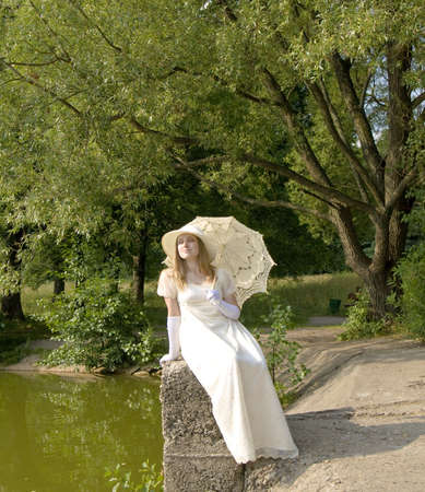 Lady in white historical dress with white umbrella near lake in park with willow trees. photo