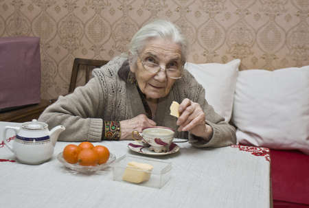 Old lady (European) drinking tea at home. Stock Photo