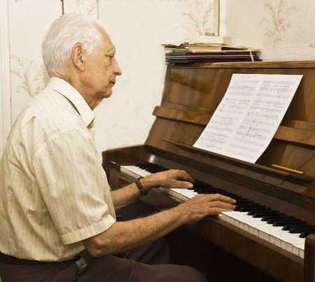 Velho (europeu) tocando piano em casa. Banco de Imagens