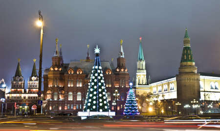 Moscow, Russia - December 15, 2011: Christmas trees on Manezhnaya square, Kremlin, Historical museum and Iverskiye gates-chapel around.