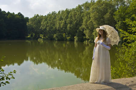 Young woman in white historical dress with white umbrella standing near lake in park. photo