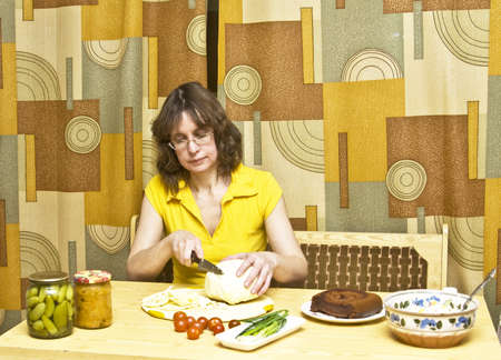Woman in kitchen sitting at wooden table cutting vegetables - cabbage, red tomatoes, green onion