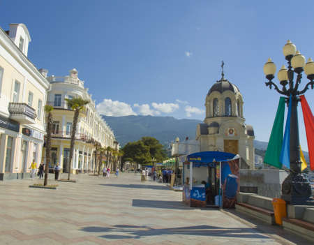 Yalta, Crimea - May 18, 2012: buildings of sea quay and chapel of Alexander Nevskiy, unidentified people on the street. Yalta is a best resort in region Crimea on Black sea, called