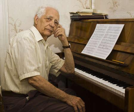 O velho sentado perto do piano.