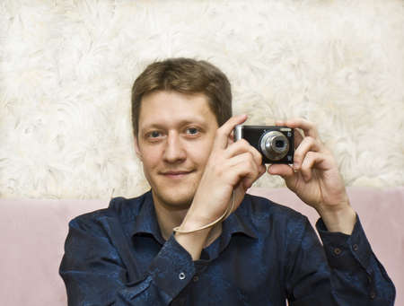 Young European man with compact camera, half body