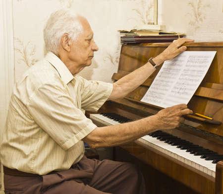 Old man sitting at piano looking at notes.