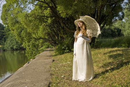 Joven hermosa dama en vestido blanco hist�rico sombrero y paraguas en la orilla del lago en el parque. Foto de archivo - 16406533