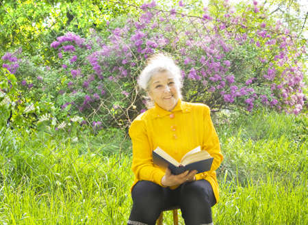 Old lady reading in garden in summer, lilac in blossom around. Stock Photo