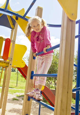 excersise: Schoolgirl Caucasian standing on sport staircase for children outdoors.