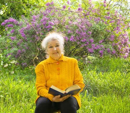 Old lady sits in garden and reads a book with lilac shrub in blossom around. Stock Photo - 17500939