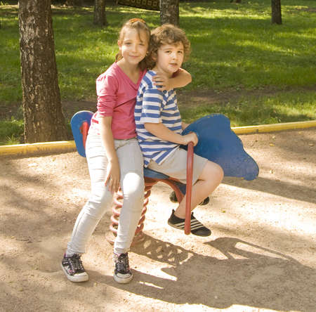 Boy and girl school age Caucasian sitting on horse-swing on yard in summer. photo