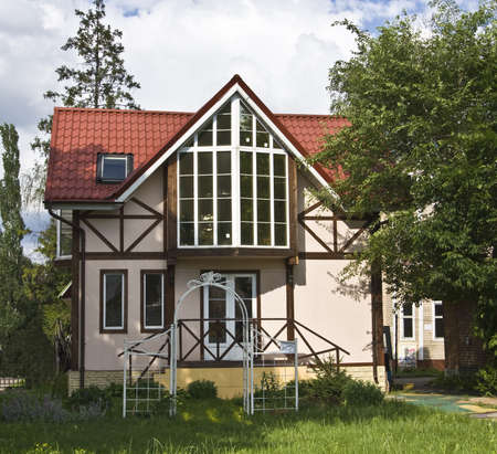 roof framework: Nice stone cottage in framework style with red tiled roof, summer time.