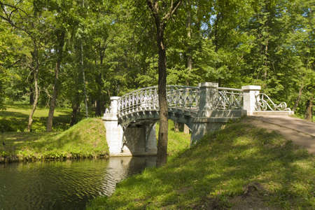 Landscape with little white bridge in park, recorded in town Gatchina in surroundings of St. Petersburg in Russia. photo