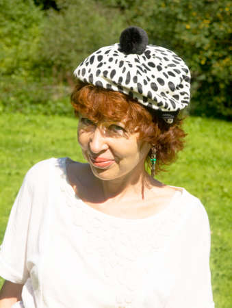 half body: Portrait of European woman with brown hair in white hat with black spots, half body.