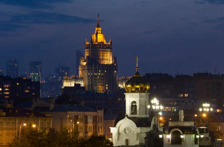 Skyscraper and chapel of cathedral of Jesus Christ Saviour at night. photo