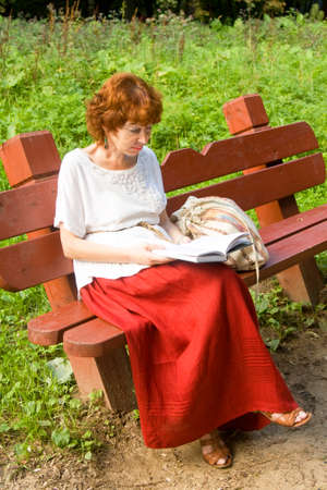 European woman with shot brown hair sitting on a bench in park reading a book. photo