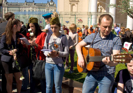gitar: MOSCOW - MAY 9, 2014  Holiday Victory Day devoted to victory in Second World War, people sing war songs on the street near Big Theatre