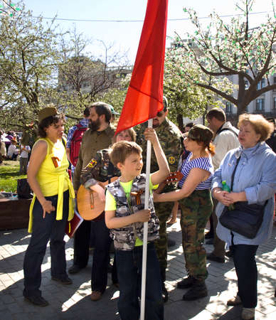 gitar: MOSCOW - MAY 9, 2014: Holiday Victory Day devoted to victory in Second World War, people singing songs of war time on the street with flags in military uniform.