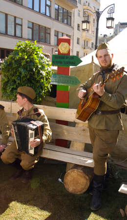 gitar: MOSCOW - MAY 9, 2014: Holiday Victory Day devoted to victory in Second World War, artists in historical military uniform play and sing on the street.