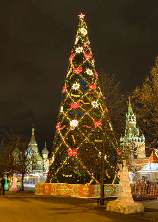 MOSCOW - DECEMBER 19, 2013: Christmas tree on Red square, ice sculptures, St. Basils Intercession cathedral and Spasskaya tower of Kremlin.