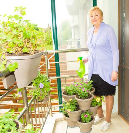 Elderly European blond lady watering flowers with watering pot on balcony.