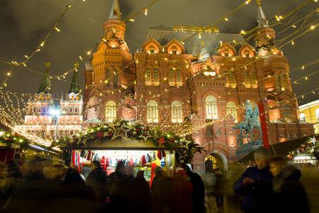 december 21: MOSCOW - DECEMBER 21, 2014: Christmas fair (market) on Manezhnaya square near Historical museum and Iverskiye gates-chapel. Editorial