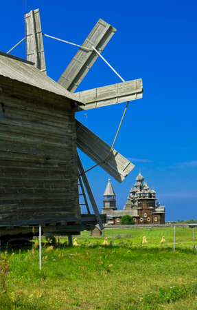 onega: Old wooden windmill and churches on island Kizhi on Onega Onezhskoye lake in region Karelia on North of Russia, UNESCO World Heritage site.
